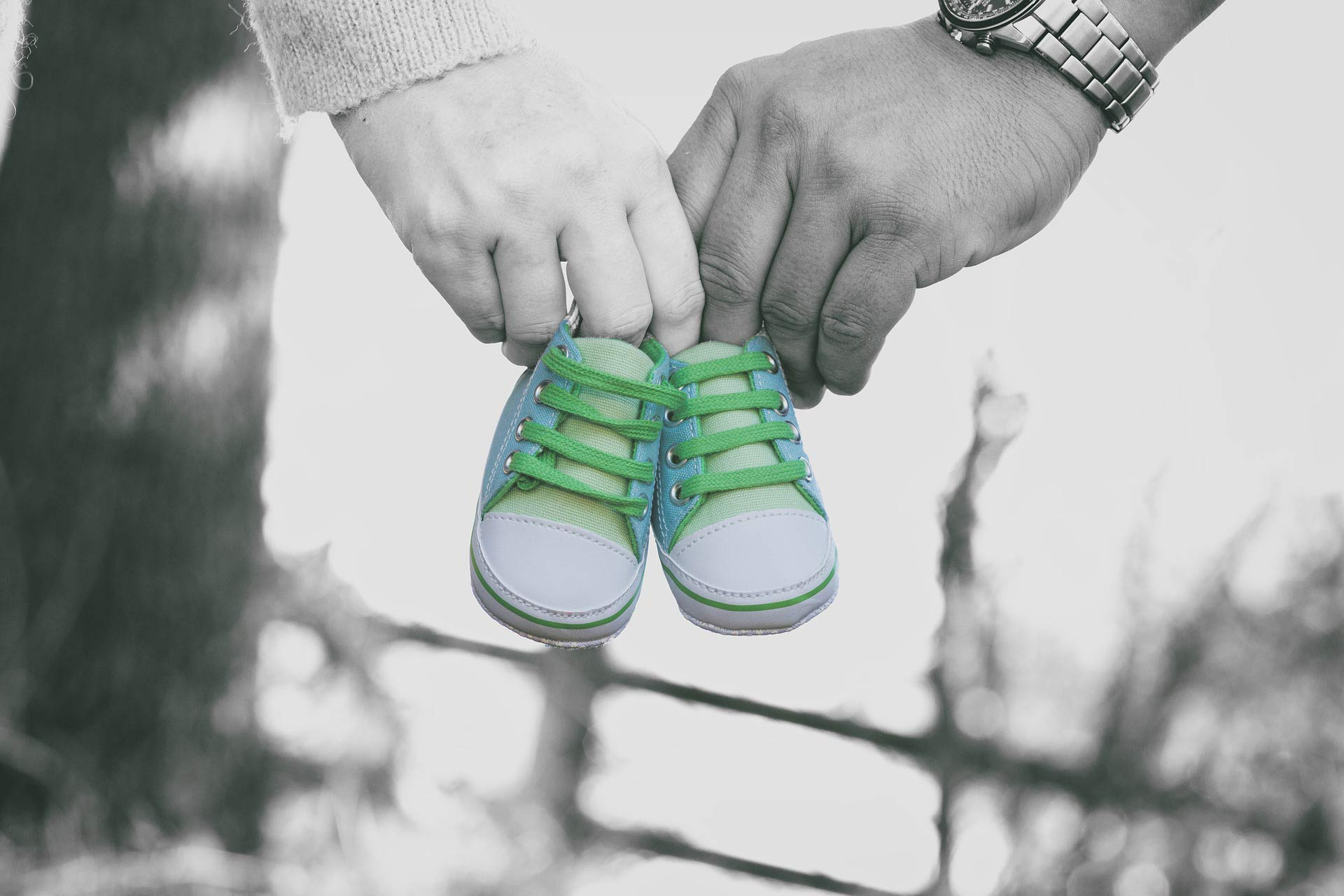 Parents holding baby shoes